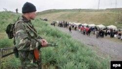 Qirg'izistonning Jalolobod viloyati Barash qishlog'i (Andijondan 40 kilometr uzoqlikda)da joylashgan birinchi o'zbek qochqinlari lagerini qirg'iz harbiysi nazorat qilmoqda. 2005 yilning 19 mayida olingan surat.