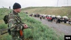 Кыргызстандын чек арачысы Бараш кыштагындагы өзбек качкындарды карап турат. 19-май, 2005-жыл