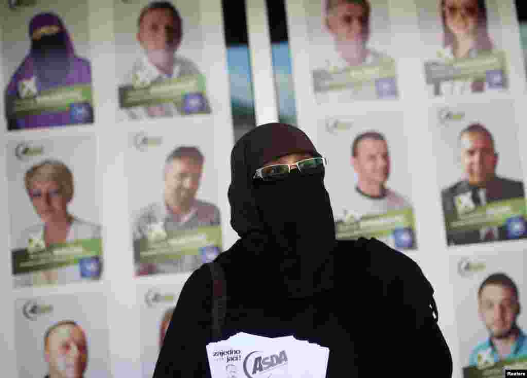 Indira Sinanovic, the first Bosnian woman to wear a niqab and run in local elections, shares promotional material in Zavidovici. (Reuters/Dado Ruvic)