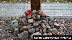 Мемориалдағы крестің түбіндегі тас пен гүл. Архангельск, 21 қыркүйек 2019 жыл.