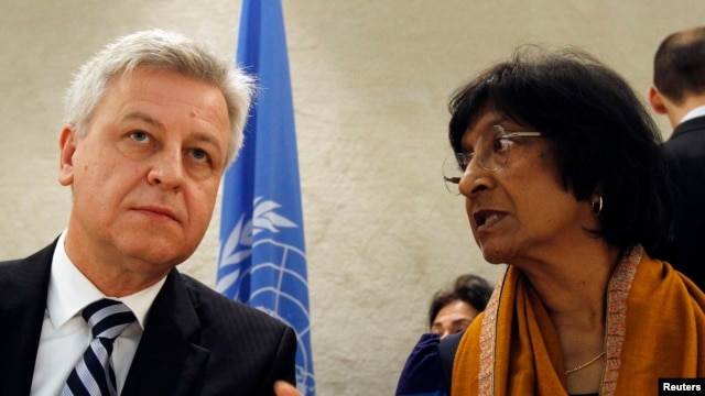 UN High Commissioner for Human Rights Navi Pillay (right) talks to Remigiusz Henczel, president of the Human Rights Council, before the 22nd session of the council at the United Nations in Geneva.