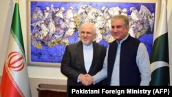 FILE: Pakistani Foreign Minister Shah Mehmood Qureshi (R) shakes hands with his Iranian counterpart Mohammad Javad Zarif in Islamabad, May 2019.