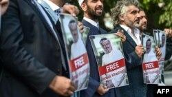 Участники акции перед посольством Саудовской Аравии в Турции стоят с плакатами с изображением Хашогги и надписью с призывом освободить его. Стамбул, 5 октября 2018 года.