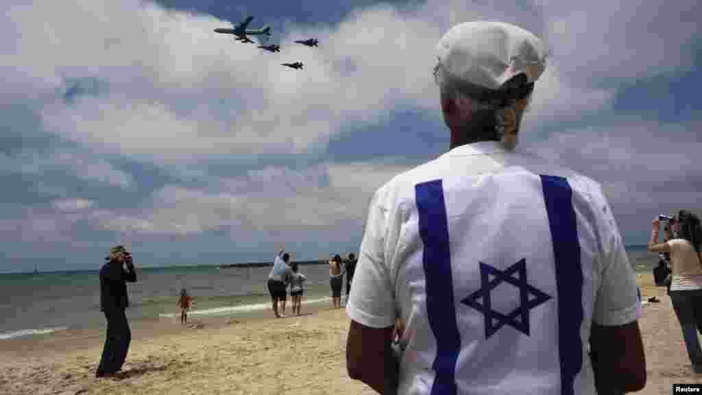 Bystanders look on as Israeli Air Force jets fly in formation over the Mediterranean Sea near Tel Aviv during celebrations for Israel's Independence Day marking the 64th anniversary of the creation of the state on April 26. (Reuters/Nir Elias)