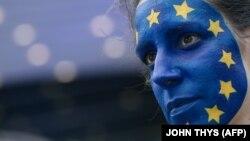 زنی با نقش پرچم اتحادیه اروپا بر چهرهاش در بروکسل