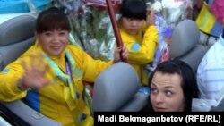 Тяжелоатлетки Майя Манеза (слева), Зульфия Чиншанло (слева от Манезы) и Светлана Подобедова в кабриолете в аэропорту Алматы, где их встретили после возвращения из Лондона. 8 августа 2012 года.