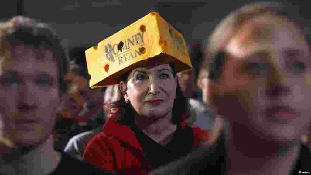 "A woman wearing a Romney-Ryan ""cheese head"" hat listens as Republican presidential nominee Mitt Romney is introduced in West Allis, Wisconsin. (Reuters/Brian Snyder)"