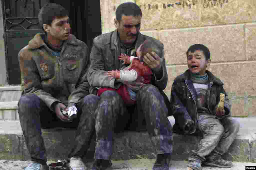A man holds a baby saved from under rubble after what activists say was an air strike by Syrian government forces in Masaken Hanano in Aleppo on February 14. (Reuters/Hosam Katan)