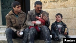 Syria -- A man holds a baby saved from under rubble, who survived what activists say was an airstrike by government forces in Masaken Hanano in Aleppo, February 14, 2014