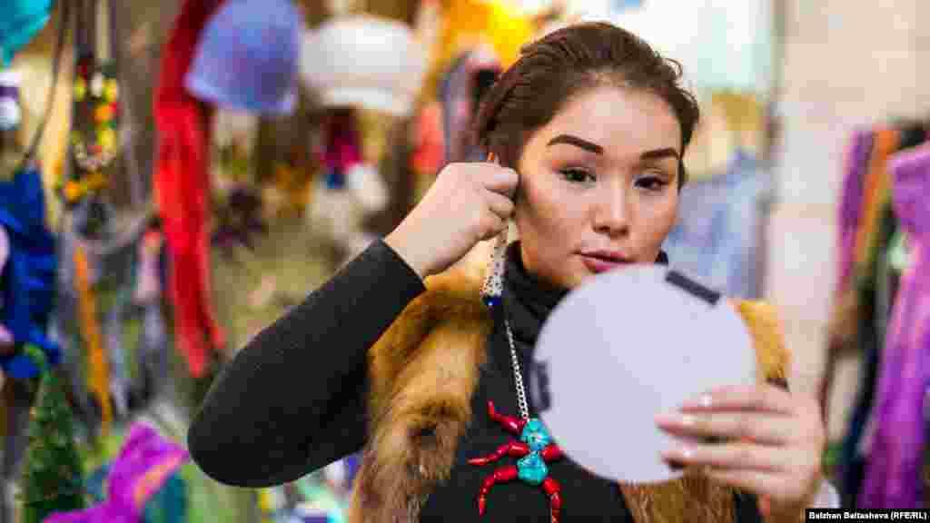Девушка примеряет украшения на «Верненской ярмарке».