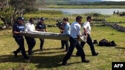 پلیس در حال حمل قطعهای که پیدا شده است