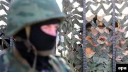 An armed man in military uniform, believed to be Russian, stands outside Ukraine's naval headquarters in Sevastopol. Inside, Ukrainian troops guard the base.