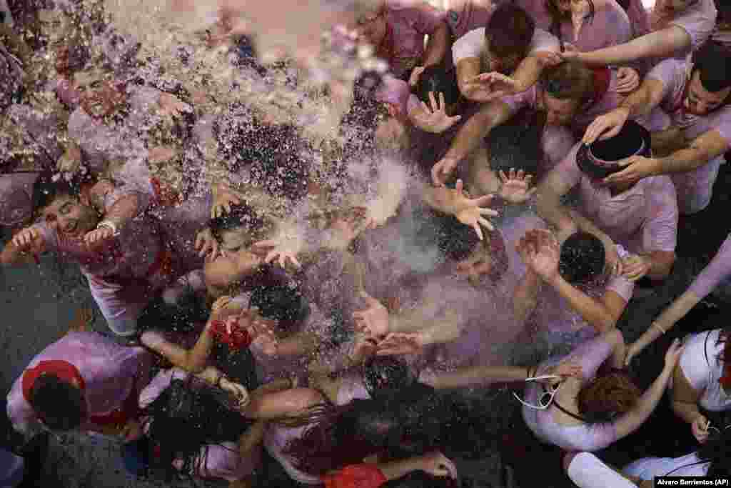 Revelers cool down as water is poured on them from people on balconies during the launch of the Chupinazo rocket to celebrate the official opening of the 2018 San Fermin festival in Pamplona, Spain. (AP/Alvaro Barrientos)