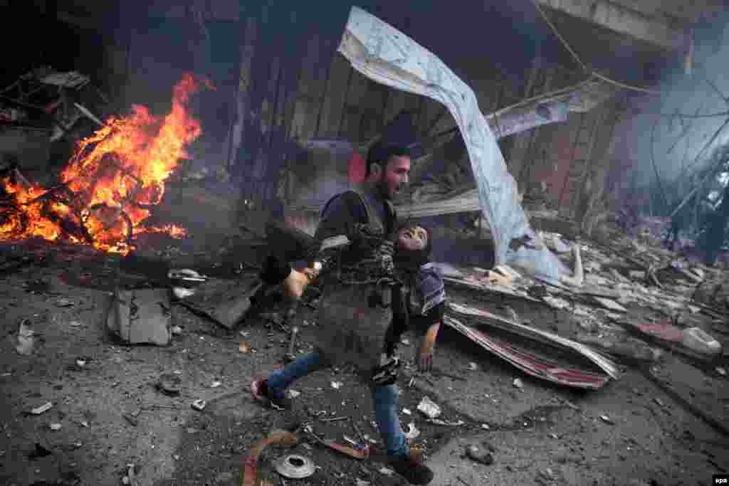 """Фотография Самира Аль-Доуми, победителя в категории """"Фотография с места события"""". Сирия, город Доума после обстрела, мужчина несет ребенка."""