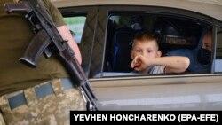 Un copil se uită spre soldații la granița regiunii separatiste Donețsk