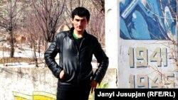 Дувана айылынын тургуну Улугбек Абдуллаев, таятасы Шаймарданкул Шаймурзаевдин ысымы жазылган эстеликтин жанында.