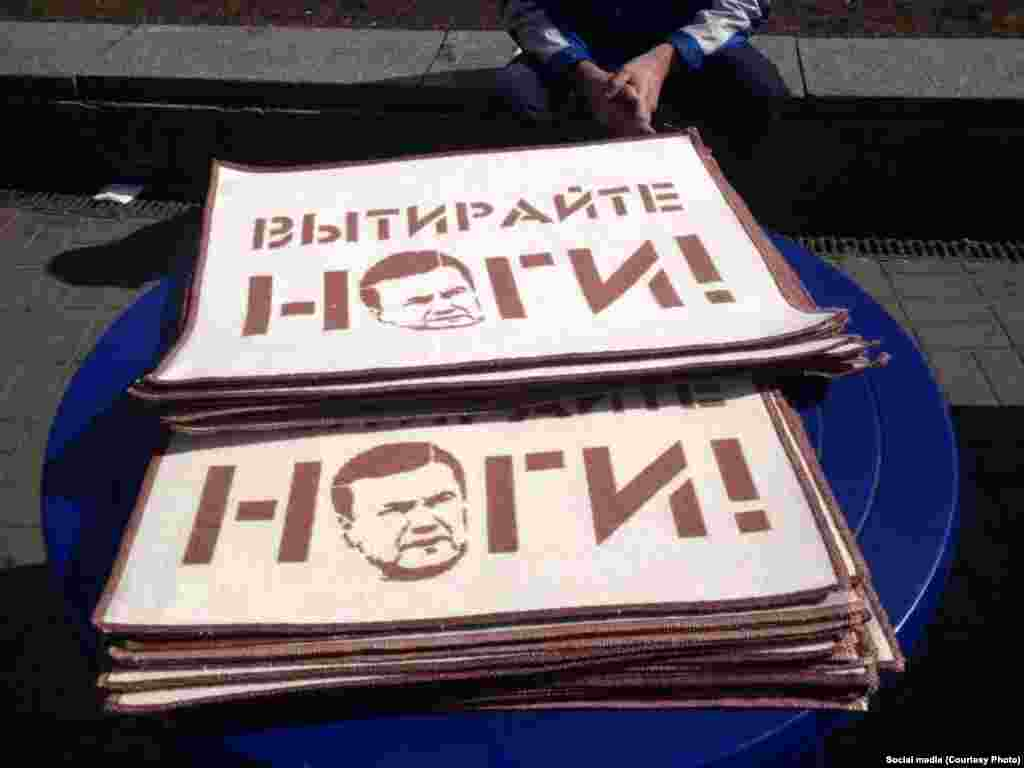 Ayaqaltı Bəli, Ukraynada ayaqaltıları da siyasətə bulaşdırırlar. Bu fotoda Kiyev sakinlərini nəyə çağırsalar yaxşıdır? - ayaqlarını devrilmiş prezident Viktor Yanukoviçə silməyə.