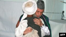 President Karzai embraces a man from Bala Buluk, where a U.S. air strike killed 140 civilians