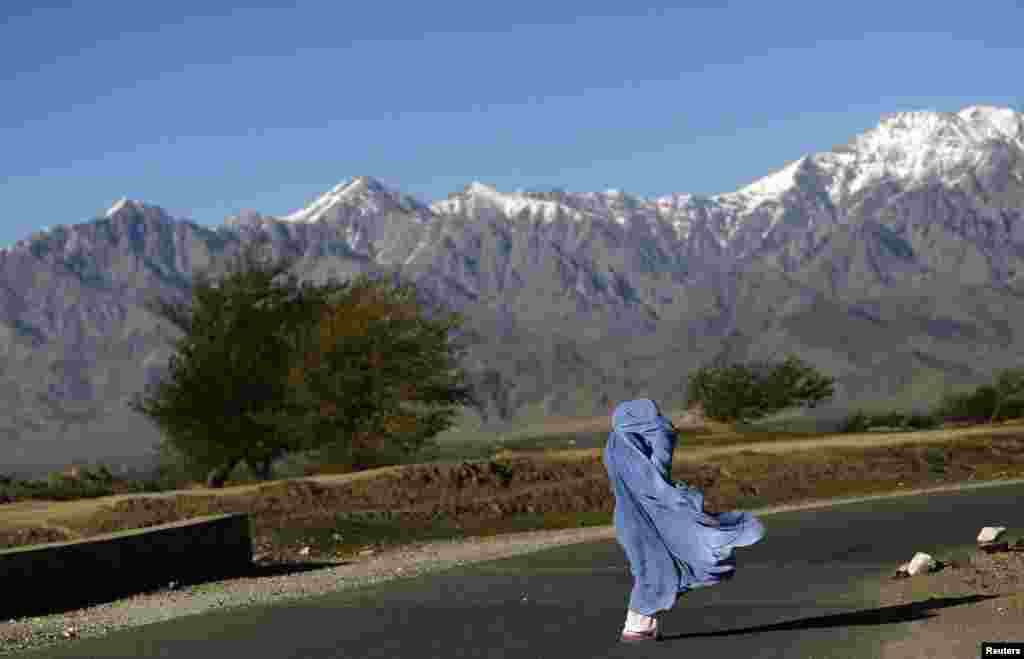 A woman in a burqa walks along a road on a windy day on the outskirts of Kabul. (Reuters/Mohammad Ismail)