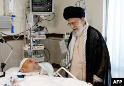 Iran's supreme leader, Ayatollah Ali Khamenei (R), visits Ayatollah Mahdavi Kani, the chairman of Iran's Assembly of Experts, lying on a hospital bed, September 15, 2014