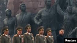 Kim Jong-un (right) stands with military officers during the unveiling ceremony of bronze statues of his father and grandfather on April 13 in Pyongyang.