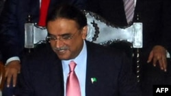 Pakistan's President Asif Ali Zardari signs a constitutional reform law during a ceremony in Islamabad.
