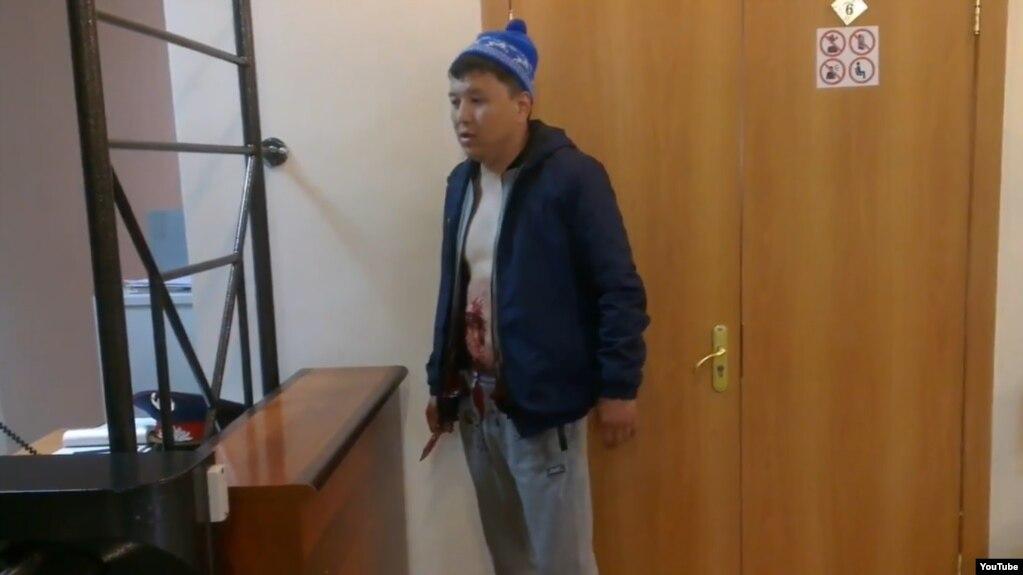 Мужчина, совершивший членовредительство, в здании суда Жезказгана. Скриншот видео. размещенного в Сети журналистом Андреем Цукановым. 17 мая 2017 года.