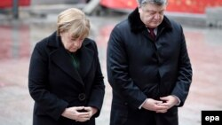 German Chancellor Angela Merkel (left) and Ukrainian President Petro Poroshenko pause for a moment at the site of the Christmas market terrorist attack at Breidscheidplatz in Berlin on January 30.