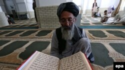An elderly Afghan reads the Koran at the beginning of Ramadan in the western Afghan city of Herat.
