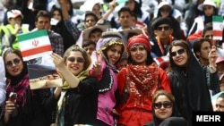Iran – Women with Iranian flags in Tehran Azadi stadium in a ceremony for honoring the organizers that facilitated cultural activities and travel inside Iran during the two-week Norouz holidays, Tehran, Apr2013