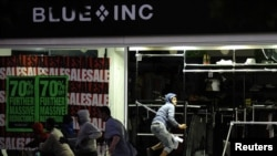 Looters run from a clothing store in Peckham, London, on August 8.