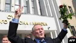 Former presidential candidate Uladzimer Nyaklyaeu raises his hands as he leaves the court building in Minsk on May 20.