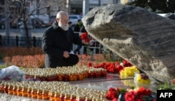 A man lays flowers at the Solovetsky Stone monument in central Moscow.