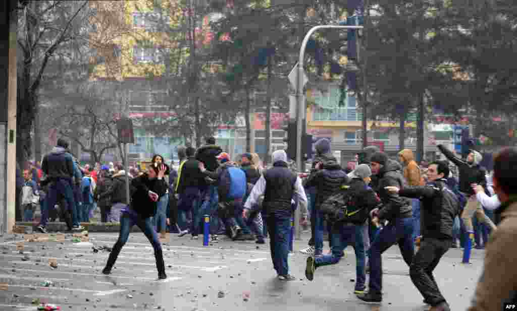 Protesters angered at Bosnia-Herzegovina's economic woes throw stones at police in front of a local government building in the northern town of Tuzla on February 6. (AFP)