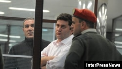 The arrest of Georgia's former Defense Minister Bacho Akhalaia (center) has given rise to speculation that a campaign is being waged against Prime Minister Bidzina Ivanishvili's political adversaries.
