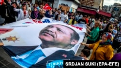 People wave a banner with a picture of Turkish President Recep Tayyip Erdogan during a gathering of supporters of his ruling Justice and Development Party (AKP) in Istanbul, Turkey, 19 June 2018