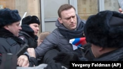 Russian opposition leader Aleksei Navalny (center) is detained by police in Moscow on January 28.