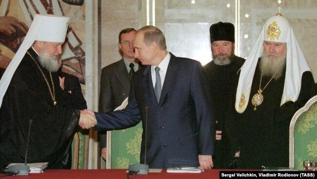 Президент Росії Володимир Путін (посередині), тодішній митрополит Смоленський і Калінінградський Кирило (ліворуч) і Московський патріарх Алексій II. Москва, 13 грудня 2001 року