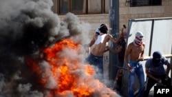 Демонстранты в масках бросают камни в израильских полицейских. Восточная часть Иерусалима, 2 июля 2014 года.