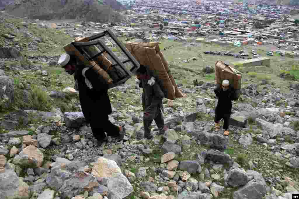 Afghan boys carry foreign-made spare car parts as they cross into Pakistan through the rugged mountainous Toorkham border crossing. (epa/Ghulamullah Habibi)