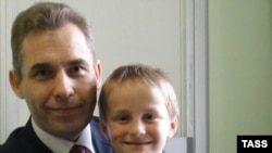 Pavel Astakhov, the Kremlin's ombudsman for children's rights, with Artyom Savelyev, who was adopted by a U.S. woman and sent alone on a flight back to Moscow