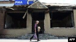 Жители Славянска проходят мимо разрушенного от взрыва здания. 24 июня 2014 года.