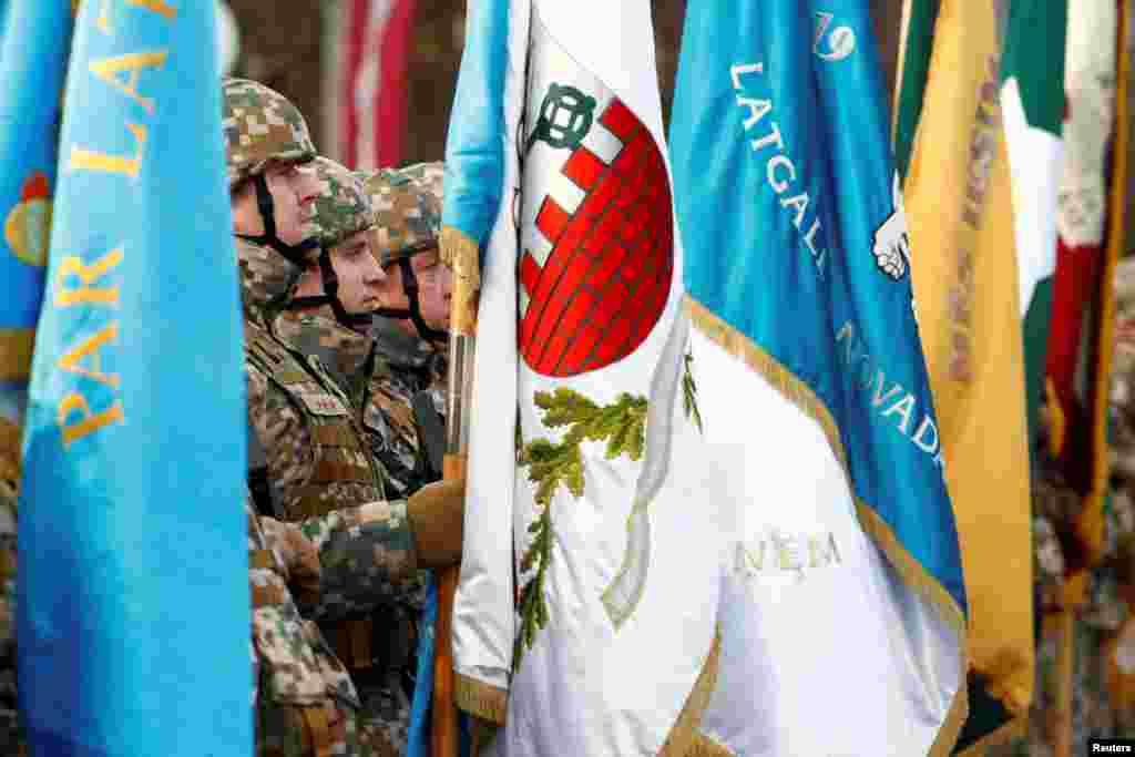 Військовослужбовці латвійської армії тримають прапори