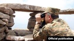 Armenia - Defense Minister Seyran Ohanian looks through binoculars at Azerbaijani army positions on the border with Armenia, 24Jul2013.