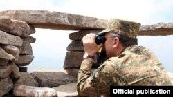 Армения - Министр обороны Армении Сейран Оганян смотрит в бинокль на позиции азербайджанской армии на границе с Арменией, 24 июля 2013 г.