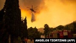 Një helikopter Sikorsky S-64hedh ujë mbi një pyll për të shuar një zjarr në fshatin Villa, në veriperëndim të Athinës, më 18 gusht 2021.
