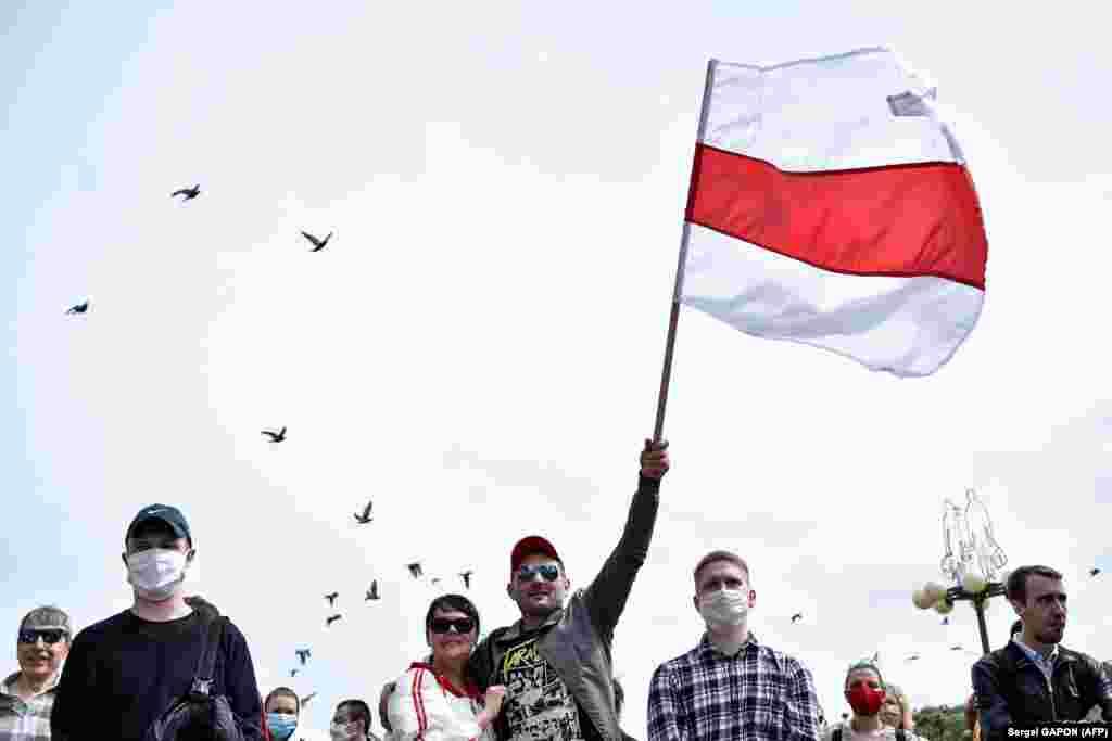 Мітингувальник махає старим білоруським прапором у Мінську під час збору підписів