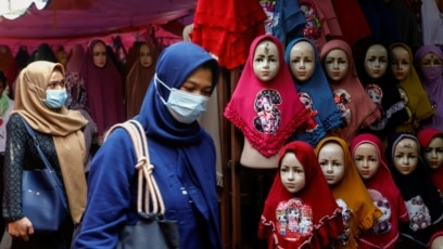 INDONESIA-HIJAB/RIGHTS/Women walk past hijabs displayed for sale at the Tanah Abang textile xafs in Jakarta, Indonesia, March 16, 2021.