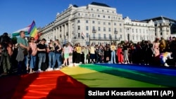 People unfurl a rainbow flag during an LGBT rights demonstration in front of the Hungarian parliament building in Budapest in June.
