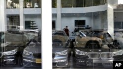 In this Sept. 17, 2018 file photo, imported cars are displayed at a showroom in Tehran, Iran. With high customs duties, these luxury cars cost 2-3 times more in Iran than in most other countries.